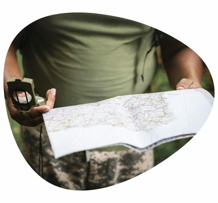 close-up of someone holding a map and compass